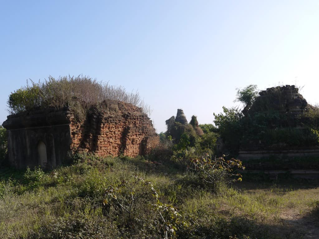 Some remaining structures with old stupas in the background.