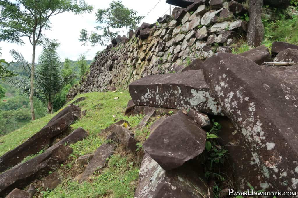 Polygonal basalt logs stacked along the side of one of the terraces.
