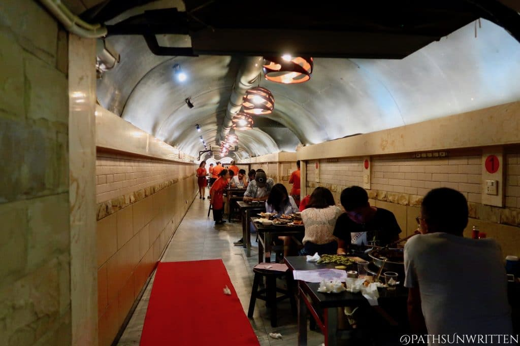The long corridor carved into the mountainside hosts many hot pot tables.