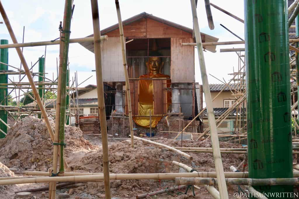 The old ubosot's Buddha statue in its protective casing.
