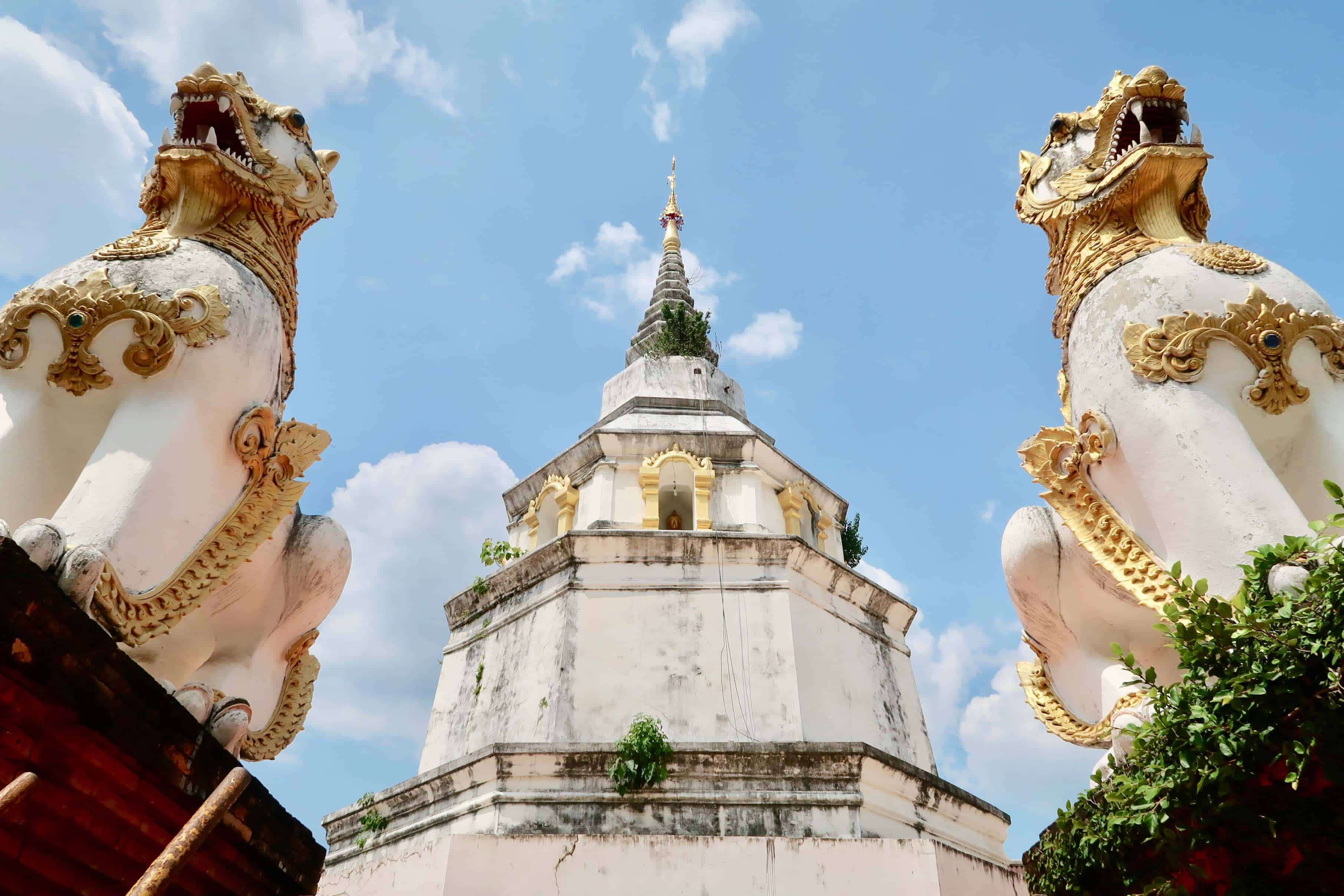 The octagonal stupa of Wat Yang Guang guarded by chinthe (singha) lion statues.