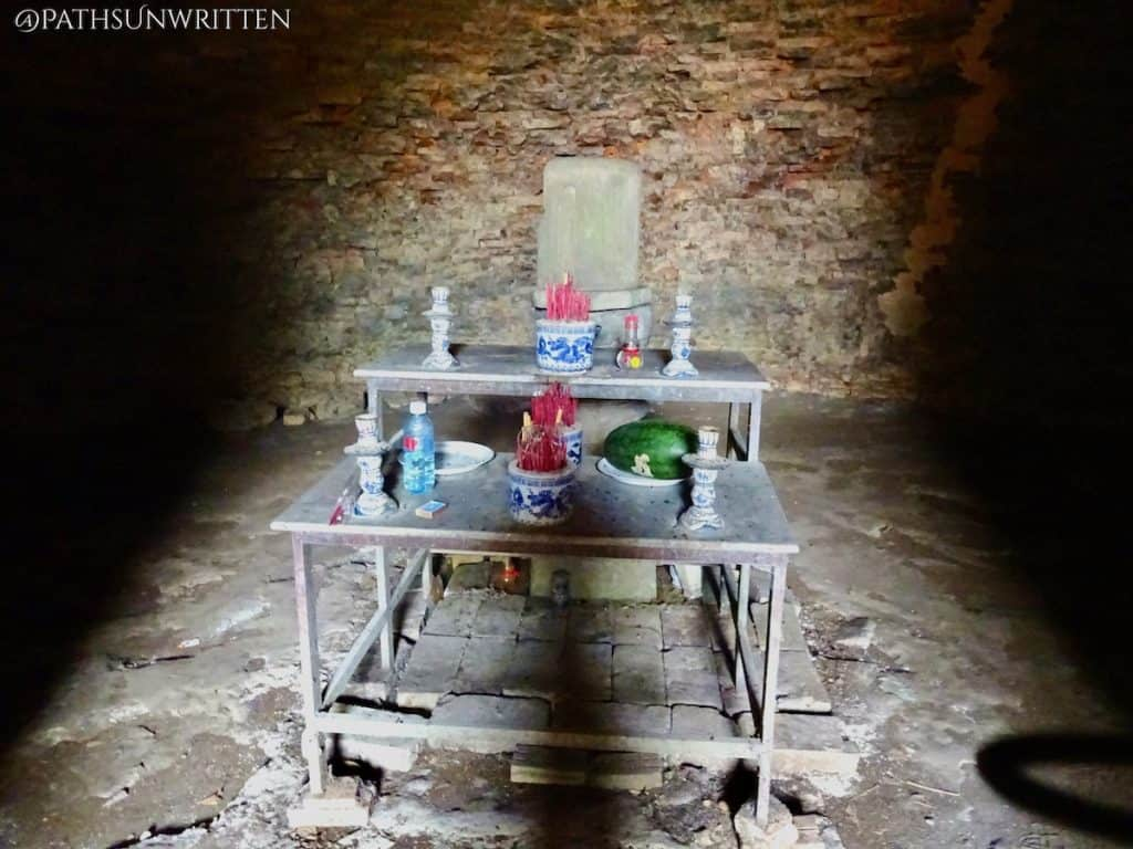 A metal altar has been placed in front of the temple's ruined lingam shrine